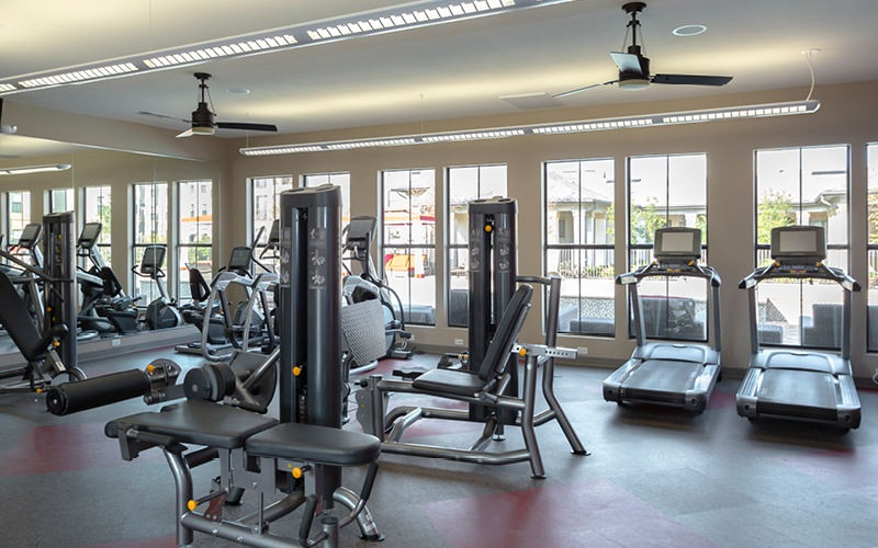 spacious fitness center with ample lighting, cardio and weight training equipment and ceiling fans