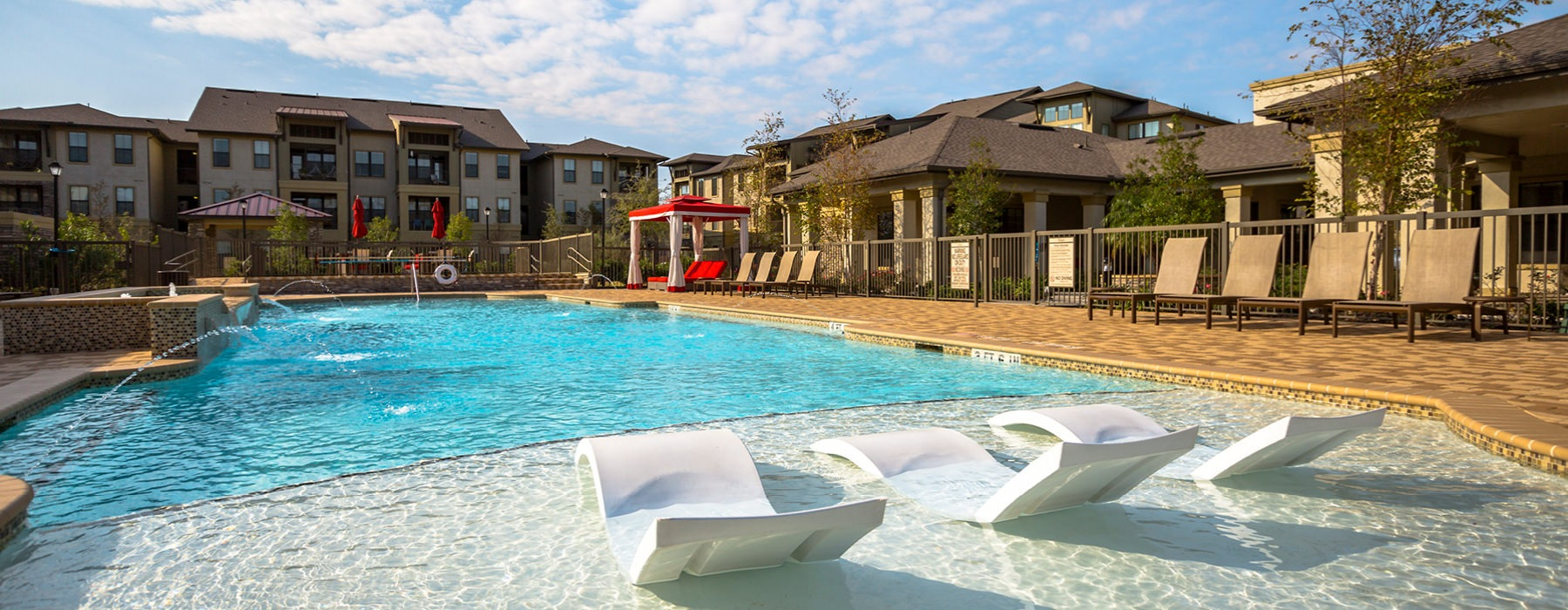 sun deck in resort style pool with lounge chairs looking across the pool and its fountains